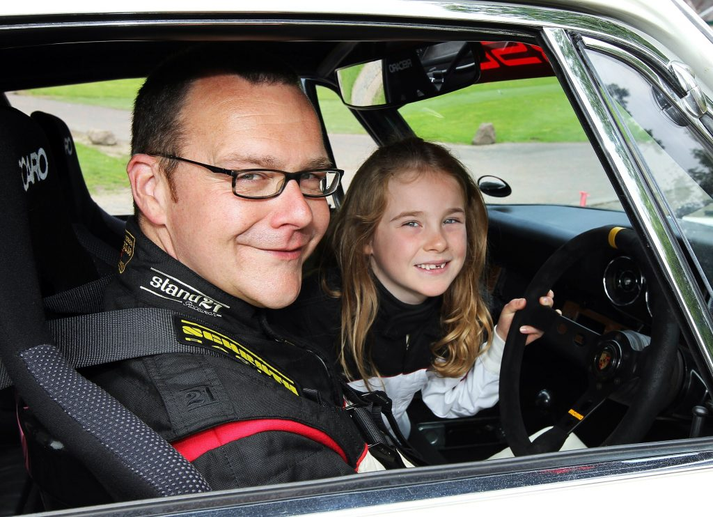 Father and daughter sitting in a classic car
