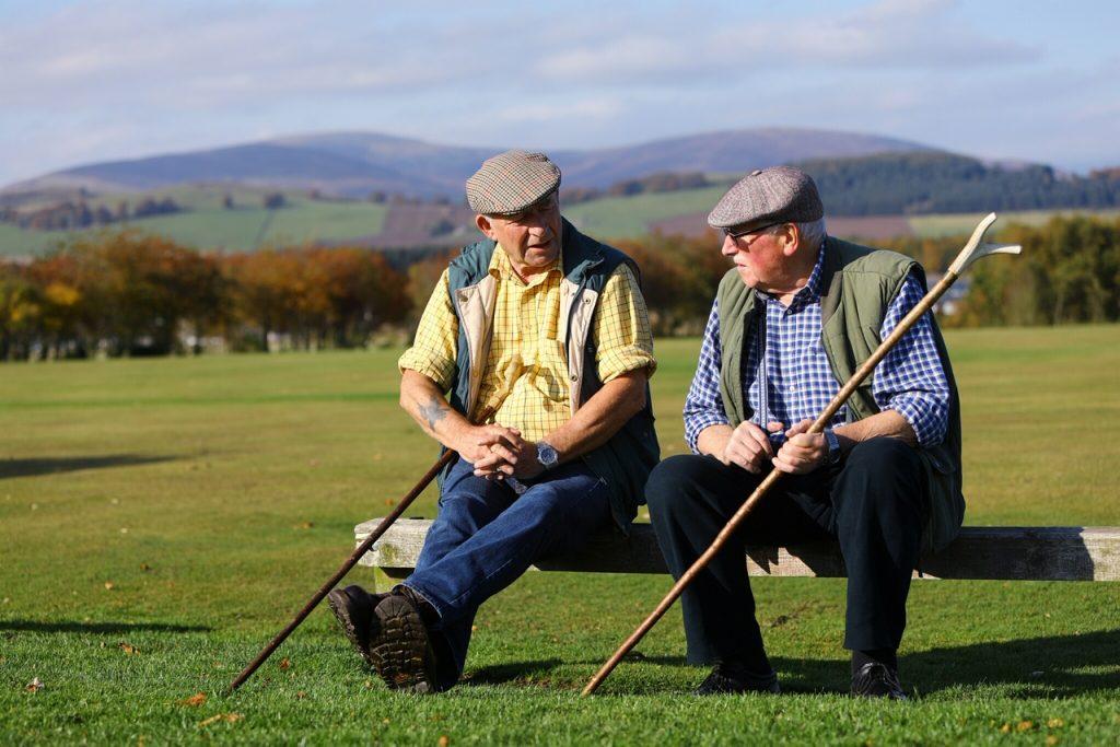 2 men sitting in a field